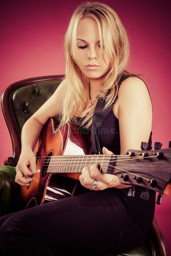 Blont kvinnasammanträde och spelagitarr royaltyfria bilder