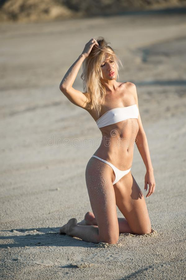 Blont kvinnasammanträde på sanden Vit bikini, sommarstil arkivbilder