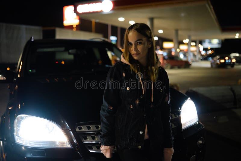 Blont kvinnaståendeanseende på natten framme av dyrt bil- lyx och mode royaltyfri bild