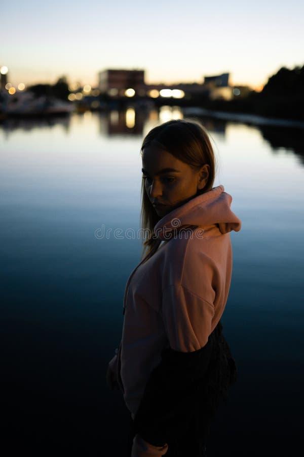 Blont kvinnaståendeanseende vid floden på natten arkivfoton