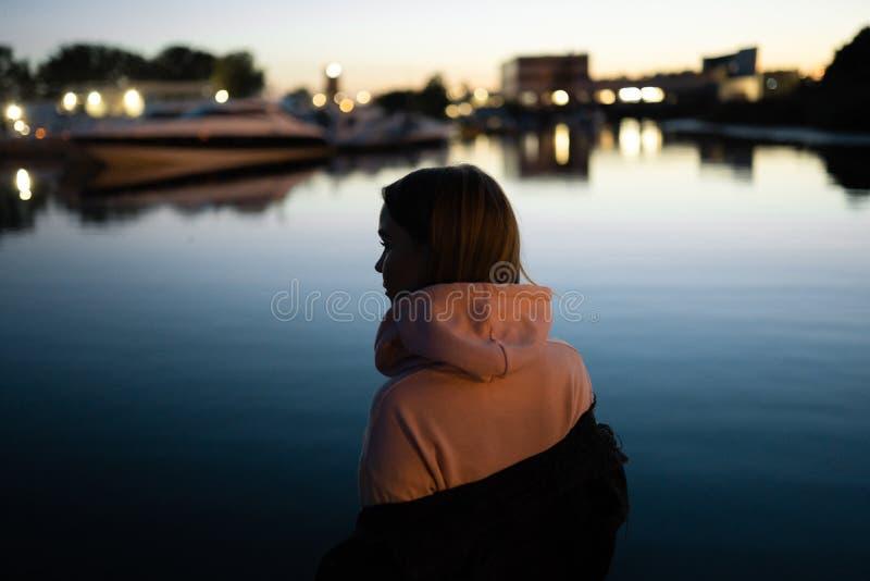 Blont kvinnaståendeanseende vid floden på natten fotografering för bildbyråer