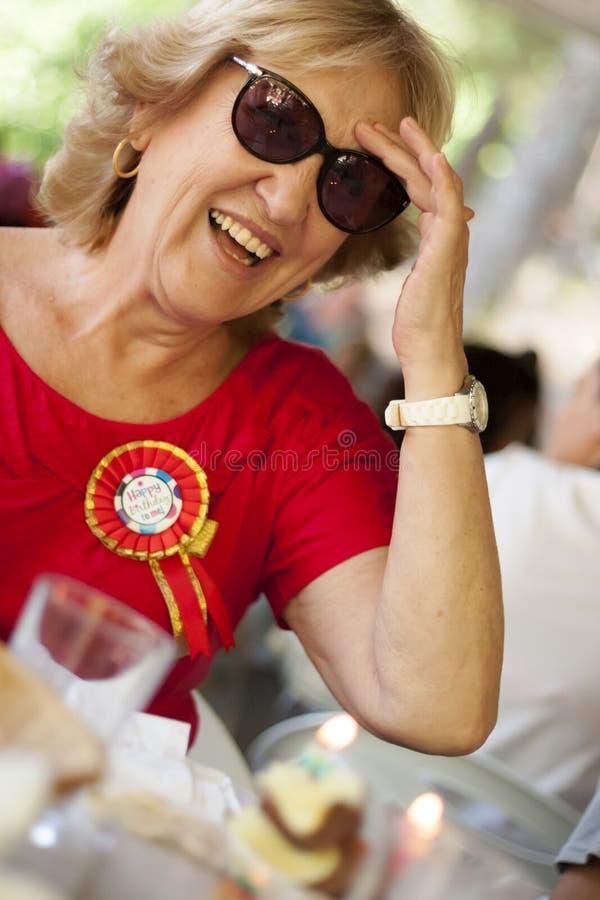 Blont le för äldre kvinna som bär en röd skjorta arkivfoton