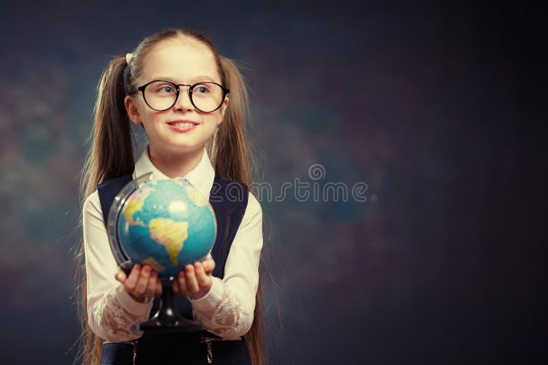 Blont litet jordklot för skolflickahållvärld i hand Färgsignal royaltyfri foto