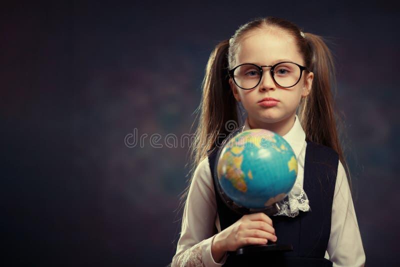 Blont litet jordklot för skolflickahållvärld i hand Färgsignal royaltyfria bilder