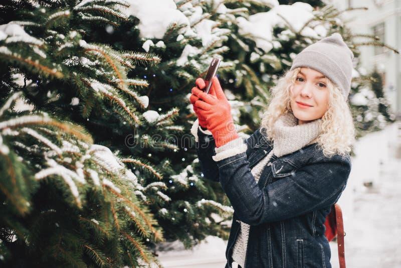 Blont lockigt flickadanandefoto på smartphonen, vinter royaltyfri bild