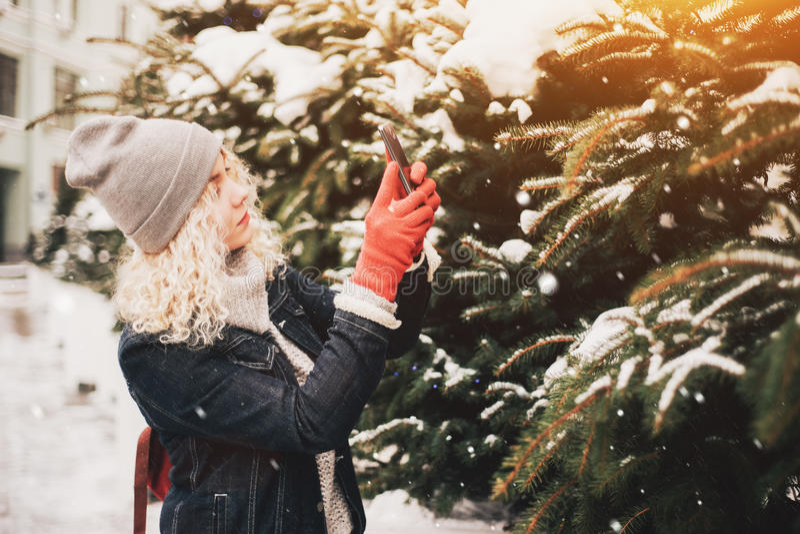 Blont lockigt flickadanandefoto på smartphonen, vinter royaltyfri fotografi