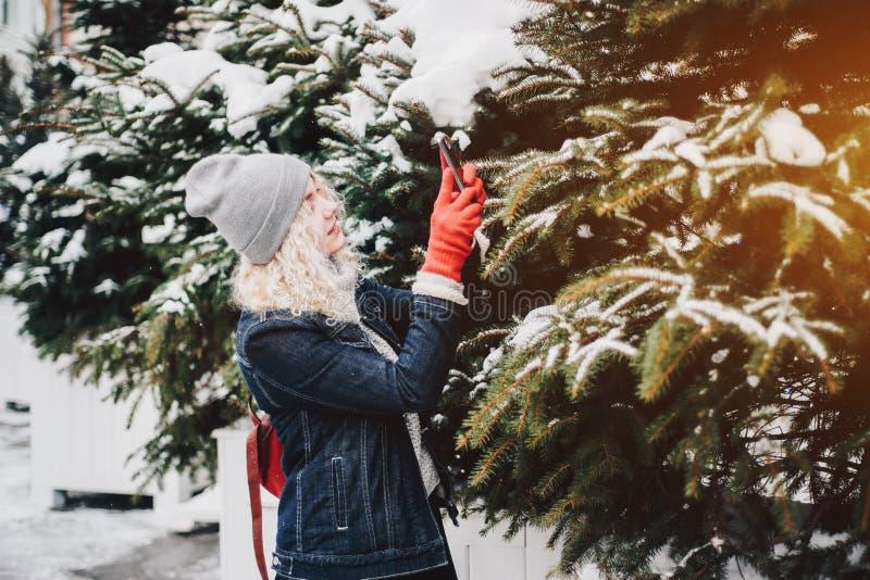 Blont lockigt flickadanandefoto på smartphonen, vinter royaltyfria foton