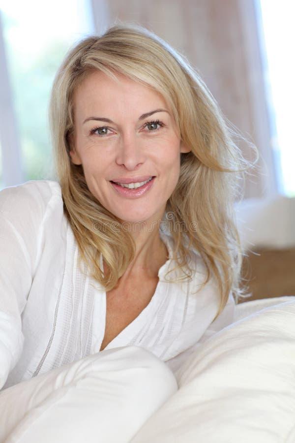 Blont moget kvinnasammanträde på soffan royaltyfria foton