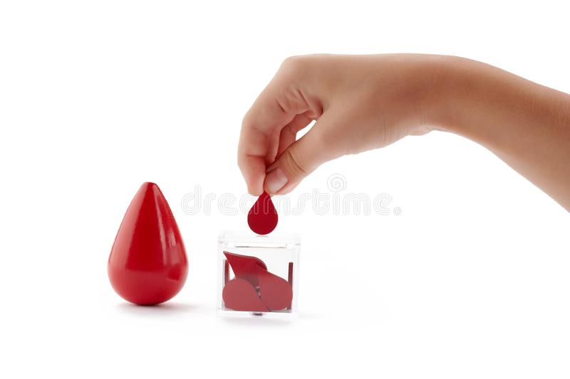 Blood donor. Hand puts drop of blood in the box as donation on white background. Concept donate blood save life. stock photography