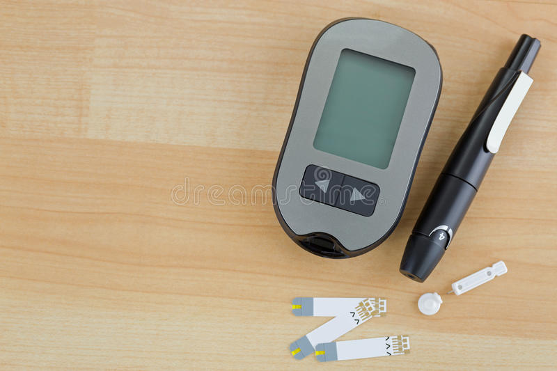 Blood Glucose meter, test strip, lancing pen device on wooden ba royalty free stock images