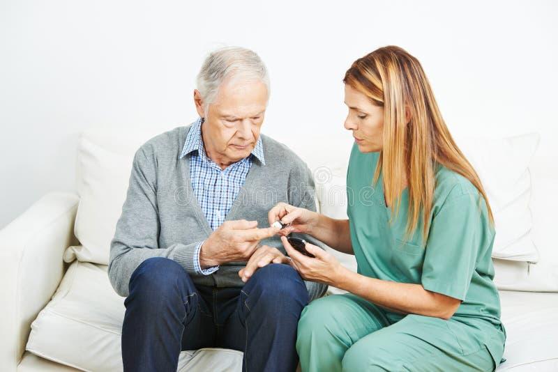 Blood glucose monitoring for senior man stock photography