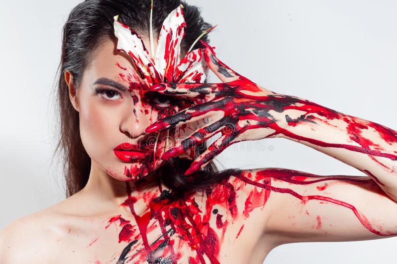 Blood Lily, scary and sexy Halloween look. Beautiful young brunette girl on white background. Blood flower, makeup face art stock photo