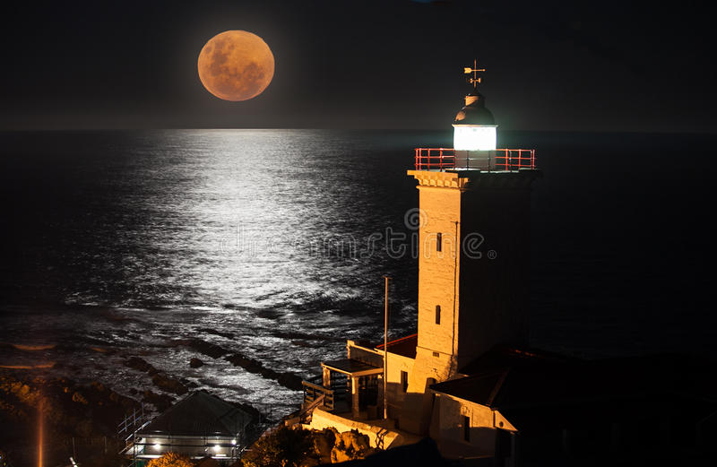 Blood moon and a black ocean. A full moon rising over the sea with a lighthouse in the foreground royalty free stock photo
