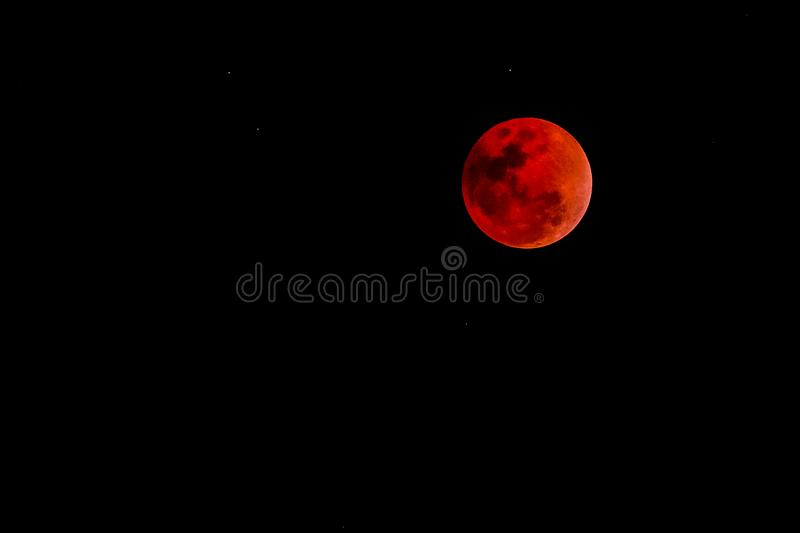 Blood moon concept of a red full moon against black sky. Blood moon concept of a red full moon against a black sky royalty free stock images