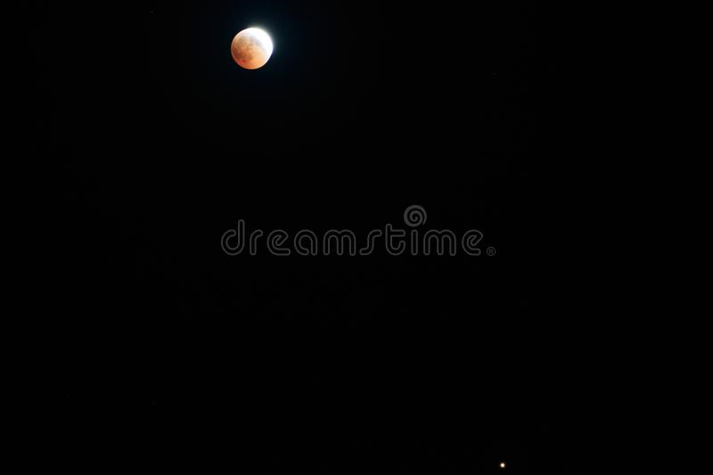 Blood Moon 2018: Longest Total Lunar Eclipse of Century in july, Moon and Mars planet opposition. Night photography. Telescopic stock images