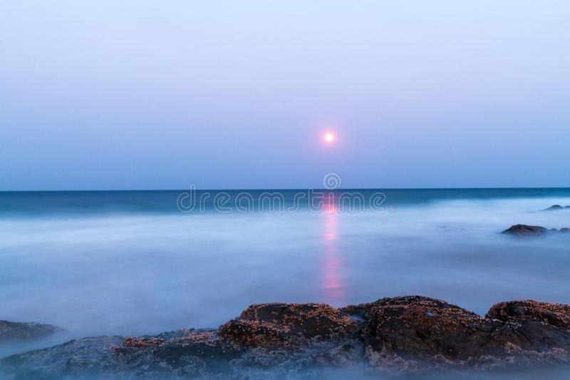 Blood moon over the sea. A long exposure of the blood moon reflects over the rocky shoreline during a cloudless evening in Snapper rocks, Queensland, Australia stock image