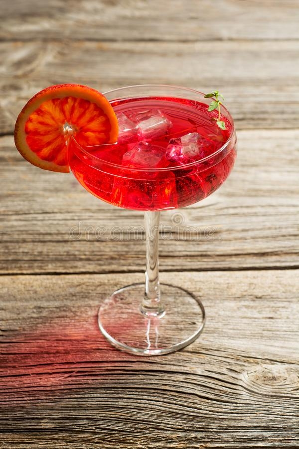 Blood Orange Margarita cocktail with ice and thyme on old wooden backgorund royalty free stock images