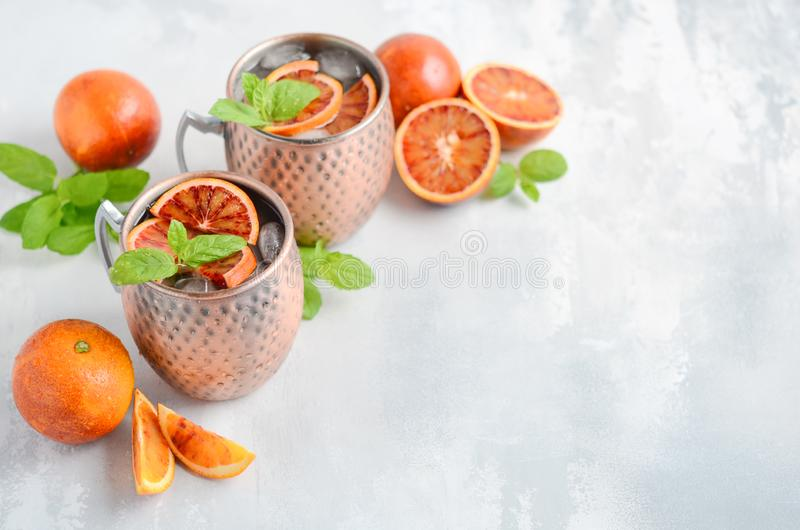Blood orange Moscow mule alcohol cocktail with fresh mint leaves and ice in copper mugs on a gray concrete background. royalty free stock image