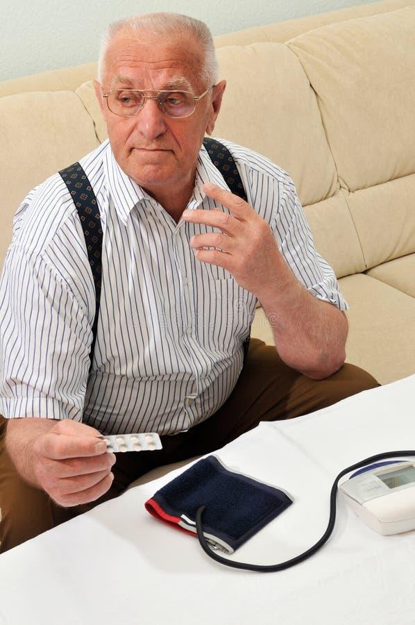 Blood pressure. Senior checking his blood pressure royalty free stock image
