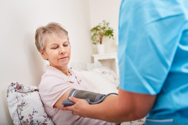Blood pressure of senior woman royalty free stock image