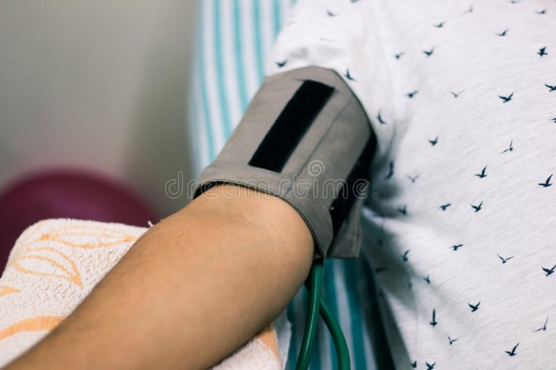 Blood pressure cuff tied in arm of a patient.  royalty free stock image