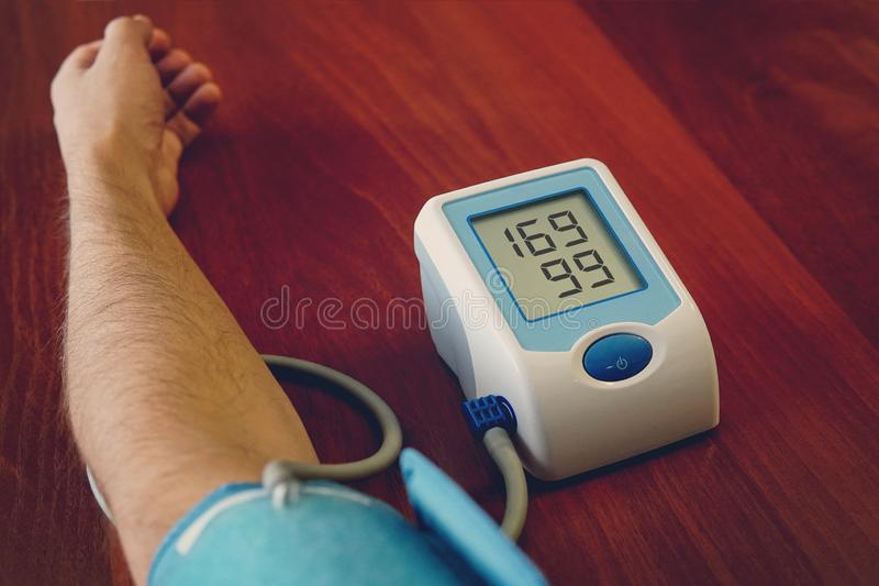 Blood pressure digital pulse monitor. Woman measuring her blood pressure and hearth rate. Health. stock photos