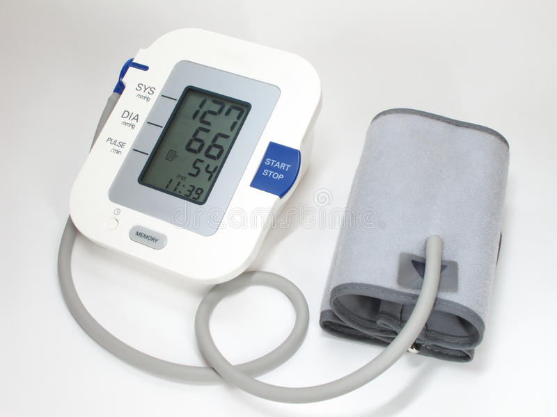 Blood pressure monitor and cuff. A modern blood pressure monitor and cuff. On white royalty free stock photo