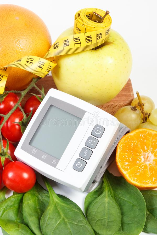 Blood pressure monitor, fruits with vegetables and centimeter, health care concept. Blood pressure monitor, fresh fruits with vegetables and tape measure stock photos
