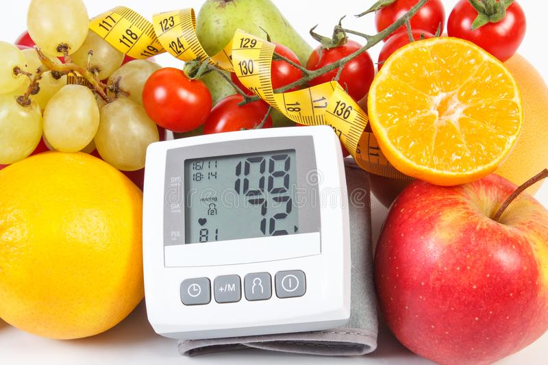 Blood pressure monitor with result of measurement, fruits with vegetables and centimeter. Blood pressure monitor with result of measurement, fresh fruits with royalty free stock photos