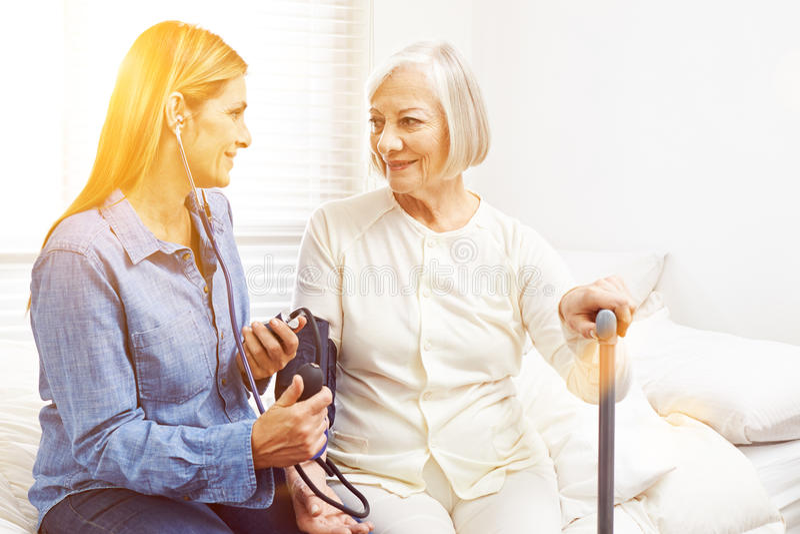 Blood pressure monitoring in nursing home royalty free stock image