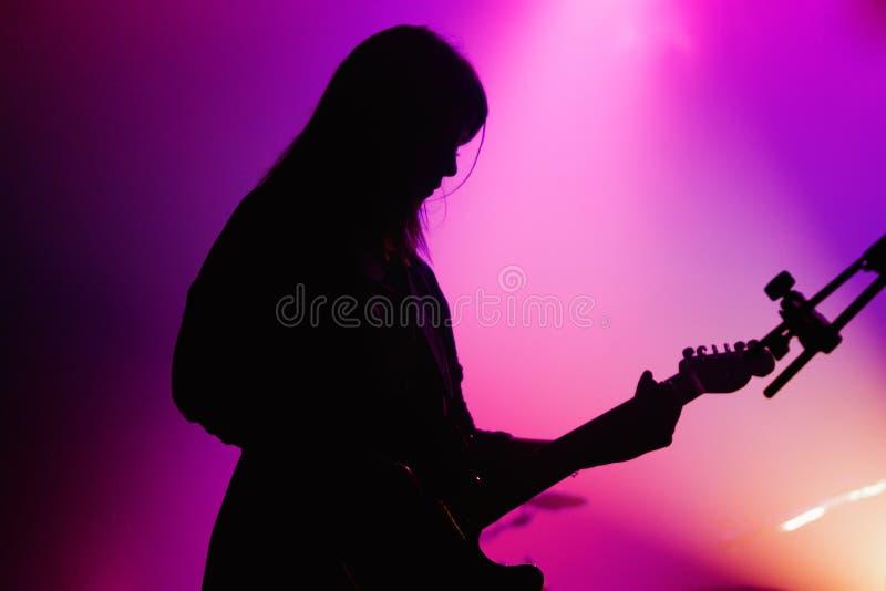 Blood Red鞋子(带)的女性吉他演奏员的剪影执行 免版税库存图片
