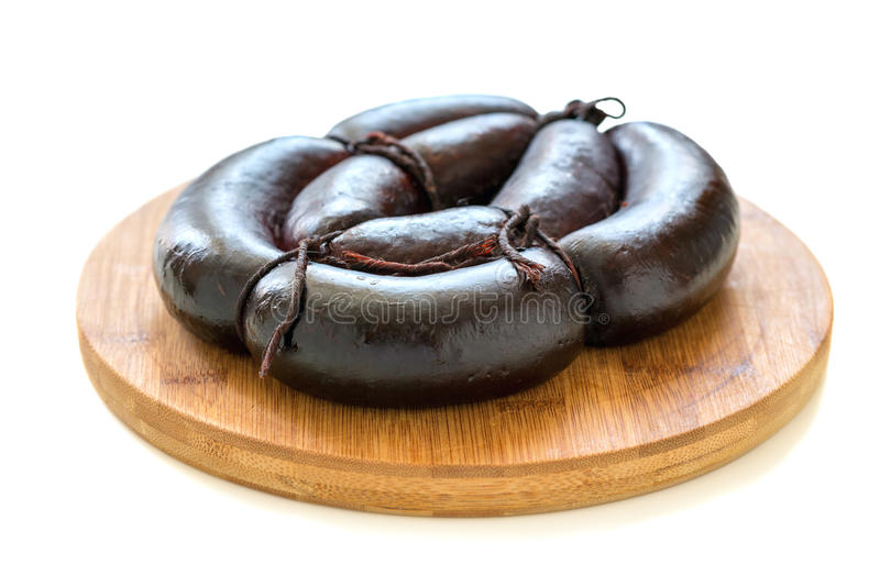 Blood sausage on a wooden stand. Wooden stand with black pudding on a white background stock photos