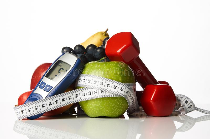 Blood sugar control with healthy organic food and dumbbells with. Blood sugar control glucometer for glucose level with healthy organic food and dumbbells with royalty free stock photos
