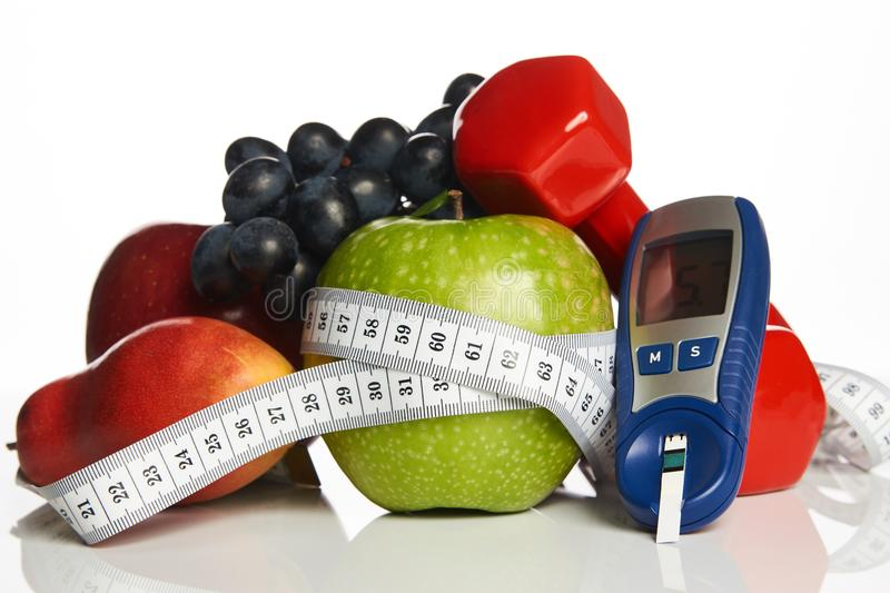 Blood sugar control with healthy organic food and dumbbells with. Diabetes monitor, cholesterol diet and healthy food eating nutritional concept with fresh royalty free stock photos