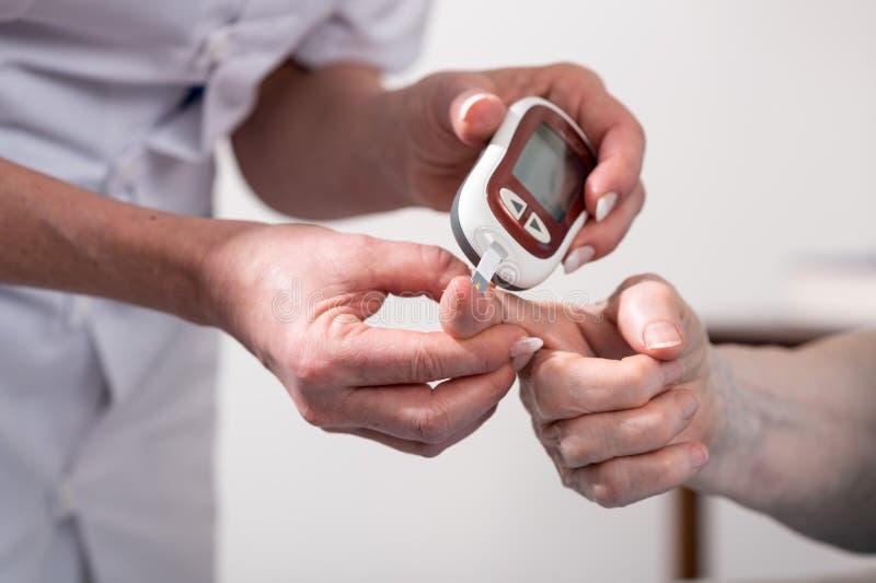 Blood sugar level checking. Nurse checking blood sugar level stock photography