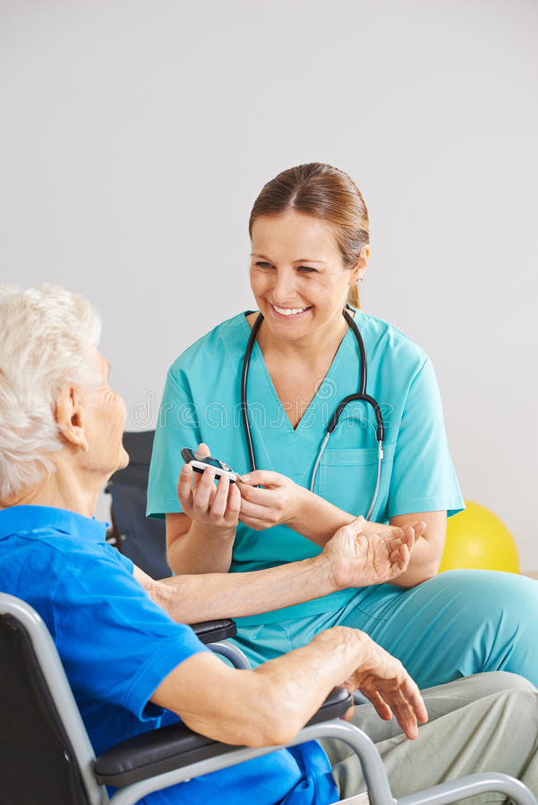 Blood sugar monitorin for diabetes patient. Geriatric caregiver doing blood sugar monitorin for old diabetes patient royalty free stock image