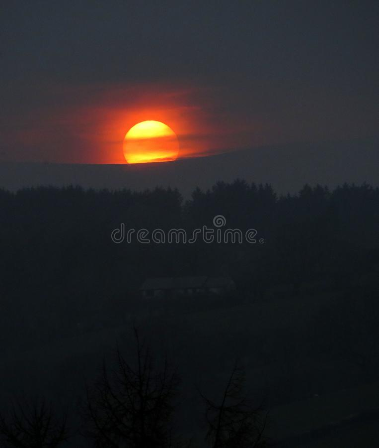 Blood sun, against dark hillside. A sun, at sunset, red, yellow, laced by cloud, poised above dark farmland royalty free stock images