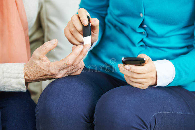 Blood test on finger of senior woman royalty free stock images