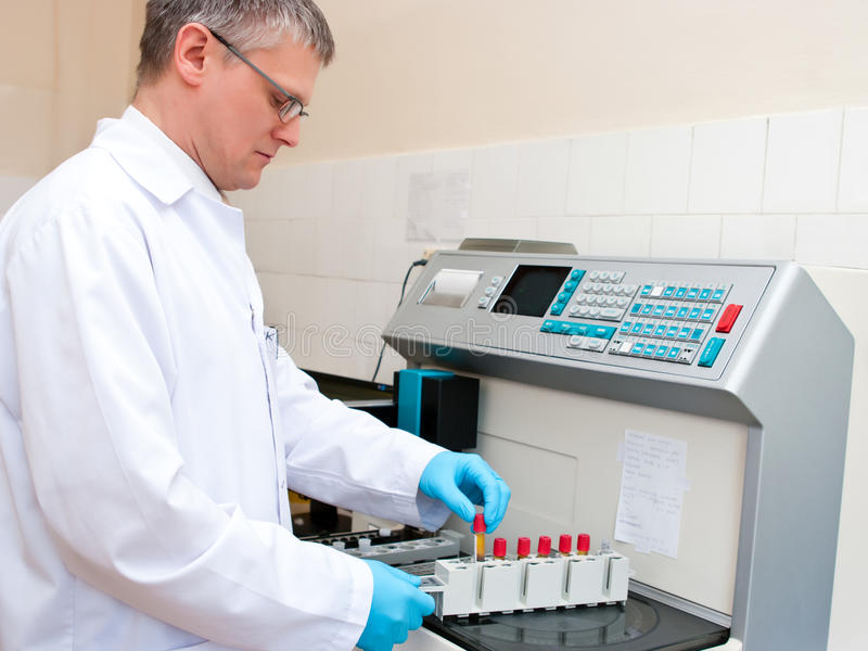 Blood test laboratory worker. Laboratory worker at blood test machine royalty free stock image