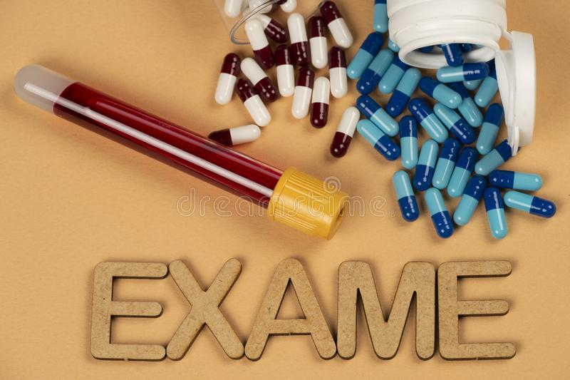 blood test vacuum tube with blue pill with the word & x22;Exame royalty free stock photo