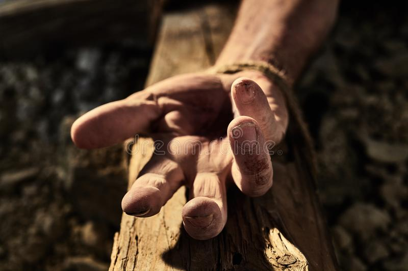 Bloodied hand with nail hole on a wooden cross. Conceptual of the martyrdom and crucifixion of Christ and his resurrection during Easter stock image
