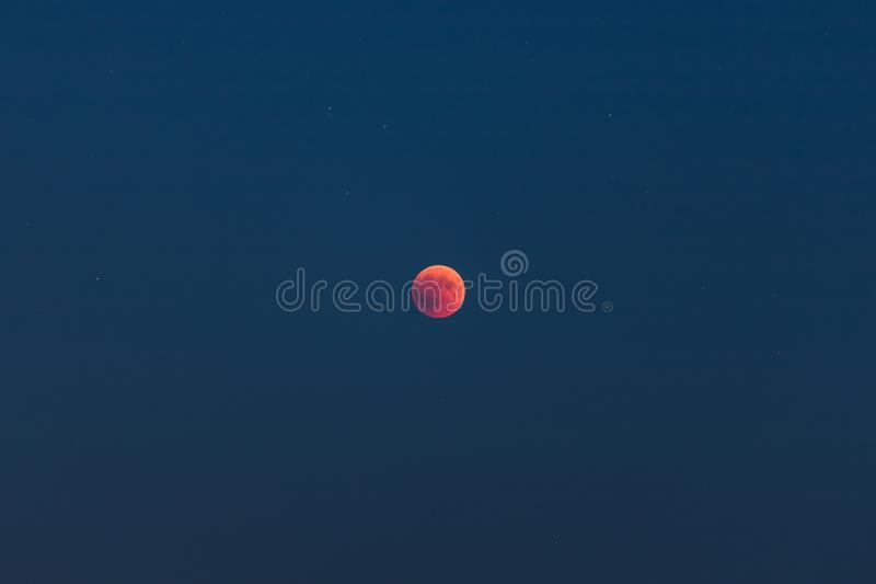 Bloodmoon or red moon phenomenon with dark sky royalty free stock image