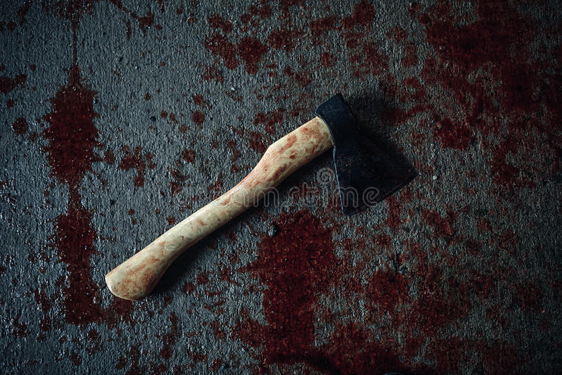 Bloody ax lying on the floor stock photos