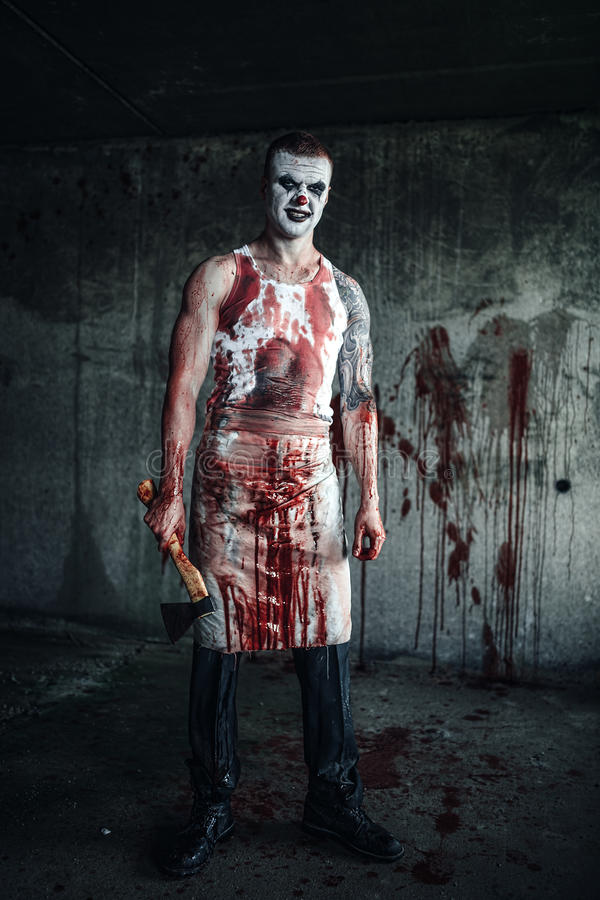 Bloody clown-maniac with ax. Crazy clown holding an ax in his hands stock image