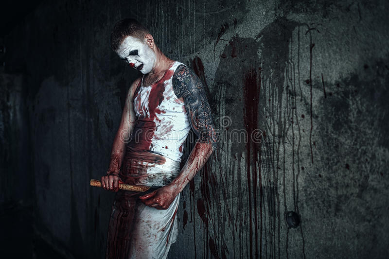 Bloody clown-maniac with ax. Crazy clown holding an ax in his hands royalty free stock photo