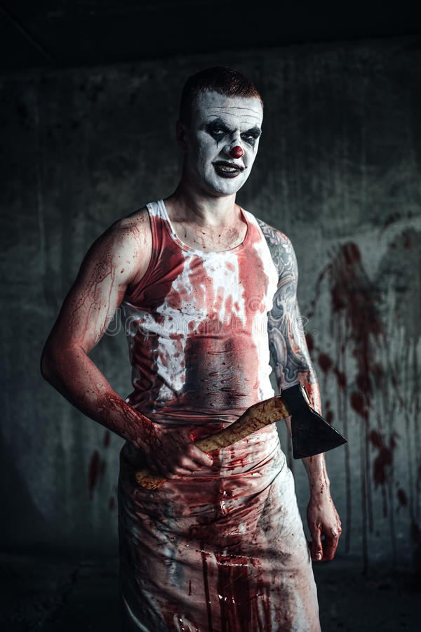 Bloody clown-maniac with ax stock photos