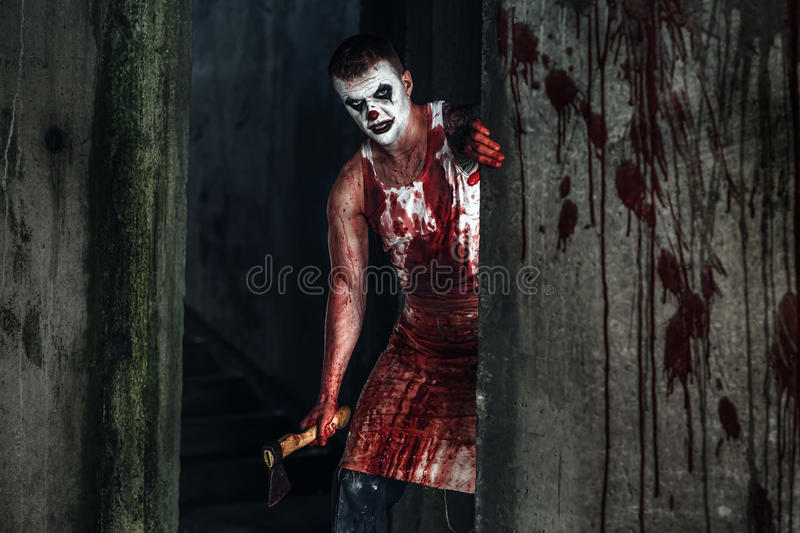 Bloody clown-maniac with ax stock image