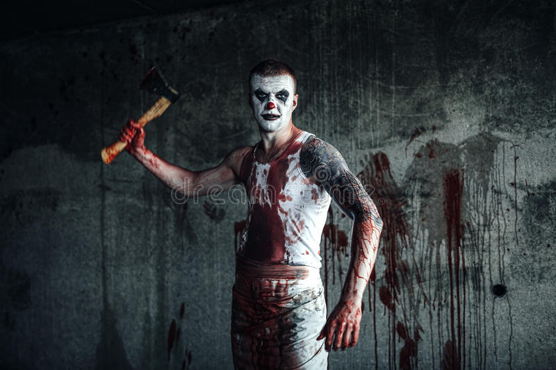 Bloody clown-maniac with ax royalty free stock images