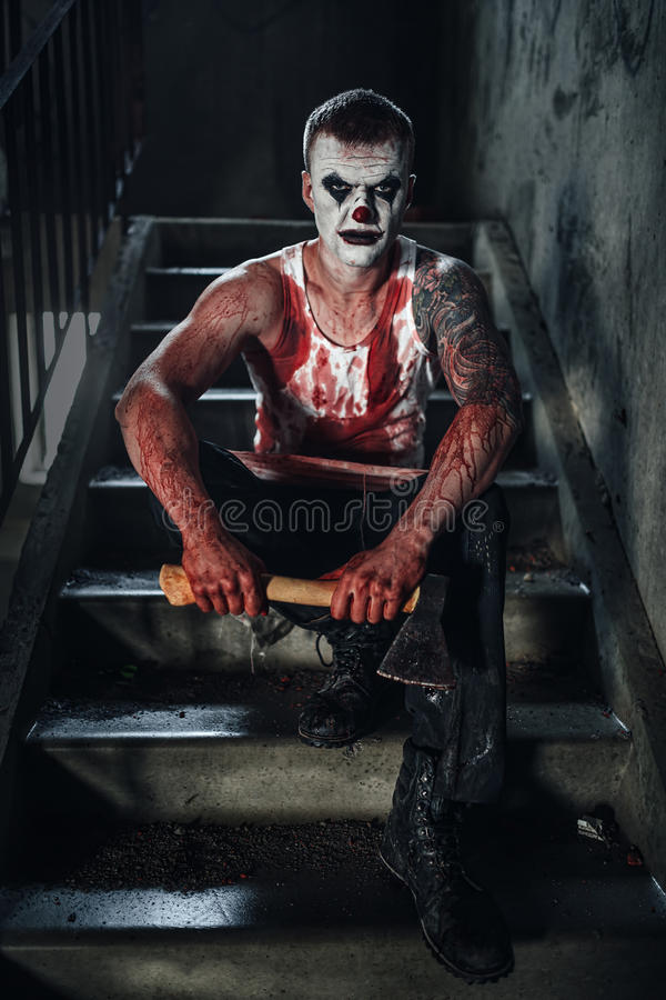 Bloody clown-maniac with ax. Crazy clown holding an ax in his hands stock images