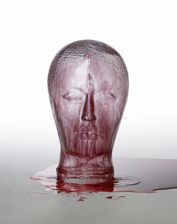 Bloody glass head. Generic human dummy head made of glass, overwhelmed with red fluid in light grey back stock photos